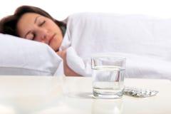 La mujer joven es enferma en cama Imagenes de archivo