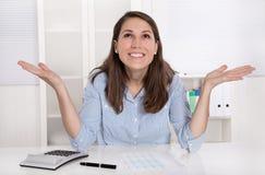 La mujer joven es feliz en el trabajo en su oficina fotos de archivo