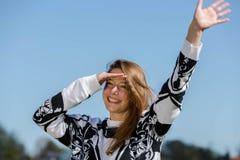 La mujer joven es feliz sobre la vuelta de sus amigos Imagenes de archivo