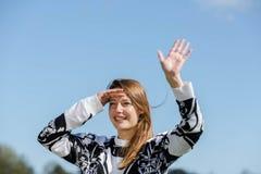 La mujer joven es feliz sobre la vuelta de sus amigos Fotografía de archivo