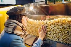 La mujer joven escoge las palomitas en el cine Comida y bocados fotos de archivo