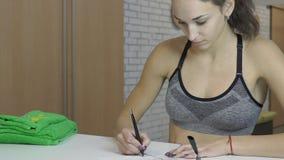 La mujer joven escribe en el papel en el mostrador de recepción en club de deportes La hembra llena el cuestionario almacen de video