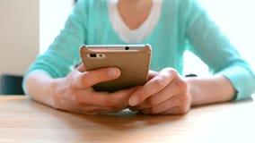 La mujer joven escribe en el teléfono móvil metrajes