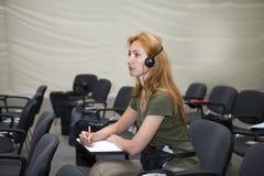 La mujer joven escucha en audiencia Imágenes de archivo libres de regalías