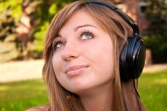 La mujer joven escucha la música Fotografía de archivo