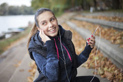 La mujer joven escucha la música por el río Foto de archivo libre de regalías