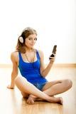 La mujer joven escucha música Fotografía de archivo