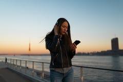 La mujer joven escucha la música en auriculares cerrados a través de su teléfono que lleva una chaqueta de cuero y vaqueros en imagen de archivo