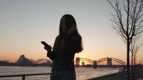 La mujer joven escucha la música en auriculares cerrados a través de su teléfono que lleva una chaqueta de cuero y vaqueros en almacen de metraje de vídeo