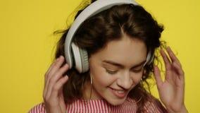 La mujer joven escucha m?sica en auriculares Muchacha feliz en auricular en amarillo almacen de video