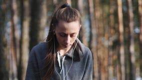 La mujer joven escucha la música en su smartphone en el bosque metrajes