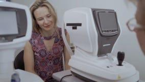 La mujer joven escucha oculista después de comprobar su vista en el equipo moderno almacen de video