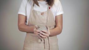 La mujer joven está amasando los pedazos de una arcilla, formando bolas, primer de manos, almacen de metraje de vídeo
