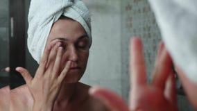 La mujer joven está aplicando la crema en el área del ojo de la cara en el cuarto de baño que mira el espejo almacen de metraje de vídeo