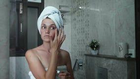 La mujer joven está aplicando la crema en el área del ojo de la cara mientras que mira el espejo almacen de metraje de vídeo