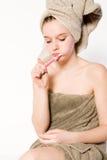 La mujer joven está aplicando sus dientes con brocha Fotos de archivo libres de regalías