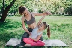 La mujer joven está ayudando a su hija a estirar Ella se está sentando detrás de su y está llevando a cabo su mano en aire mientr Imagen de archivo libre de regalías