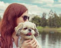 La mujer joven está caminando con su perro -- instagram entonado (perro en f fotografía de archivo