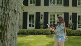 La mujer joven está caminando feliz en parque en hierba verde metrajes