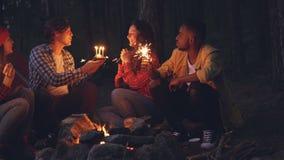 La mujer joven está celebrando cumpleaños en bosque con los amigos que soplan velas en la torta y que aplauden las manos mientras metrajes