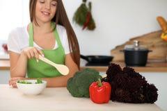 La mujer joven está cocinando la comida sana de verduras en la cocina Ciérrese para arriba de ama de casa con señalar de madera d Imagen de archivo libre de regalías