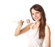 La mujer joven está comiendo el sushi Imagenes de archivo