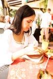 La mujer joven está comiendo en restaurante Fotografía de archivo