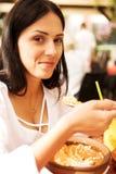 La mujer joven está comiendo en restaurante Fotos de archivo libres de regalías