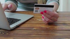 La mujer joven está comprando ropa en línea usando tarjeta de crédito y el ordenador portátil falsos metrajes