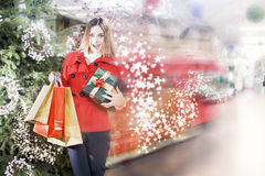 La mujer joven está corriendo dentro de una tienda de regalos de la Navidad fotografía de archivo