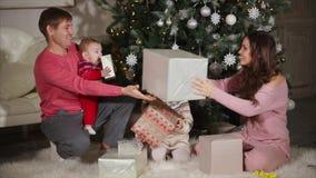 La mujer joven está dando los regalos de la Navidad a su hijo del marido, de la hija y del bebé metrajes