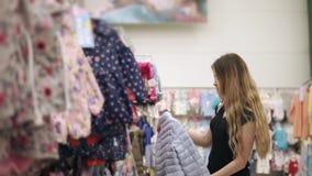 La mujer joven está dando un paseo a lo largo de los estantes con ropa de los niños en una tienda almacen de metraje de vídeo
