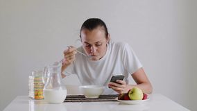 La mujer joven está desayunando y está mirando en smartphone almacen de metraje de vídeo