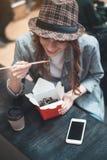 La mujer joven está disfrutando de comidas orientales Imagen de archivo libre de regalías