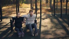 La mujer joven está ejercitando al aire libre con sus brazos deportivos del entrenamiento del novio usando barrases paralelas baj metrajes