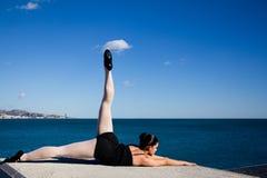 La mujer joven está ejercitando su flexibilidad en un bloque de piedra grande delante del mar Mediterráneo Imagen de archivo