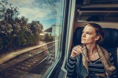La mujer joven está en el tren y los relojes a través de la ventana o Foto de archivo libre de regalías