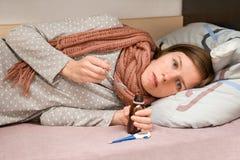 La mujer joven está enferma Ella cogió frío, sintiéndose mal y tomando medicinas imagenes de archivo