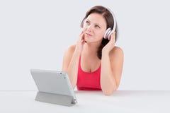 La mujer joven está escuchando la música Imagen de archivo libre de regalías