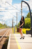 La mujer joven está esperando un tren Fotos de archivo