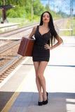 La mujer joven está esperando un tren Imágenes de archivo libres de regalías