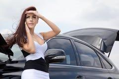La mujer joven está experimentando cerca del coche Imagenes de archivo