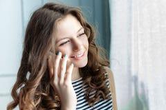 La mujer joven está hablando en el teléfono Fotografía de archivo libre de regalías
