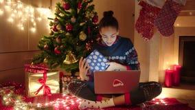 La mujer joven está hablando en línea con su familia usando el ordenador portátil el noche de los Años Nuevos Ella se está sentan metrajes
