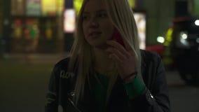 La mujer joven está hablando por el teléfono en la calle almacen de metraje de vídeo