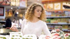 La mujer joven está haciendo compras en el centro comercial almacen de video