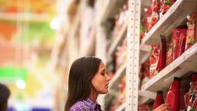 La mujer joven está haciendo compras en supermercado choosing metrajes