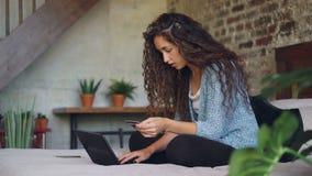 La mujer joven está haciendo el pago que sostiene la tarjeta de banco y que trabaja con el ordenador portátil que se sienta en ca almacen de metraje de vídeo