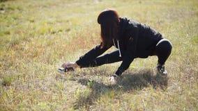 La mujer joven está haciendo los ejercicios para estirar sus piernas en un campo en día soleado metrajes
