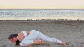 La mujer joven está haciendo shvanasana del mukha de Adho de la yoga con el pie aumentado en la playa de la arena en la salida de metrajes